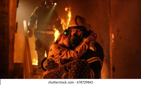Burning Building. Group Of Firemen Descend on Burning Stairs. On foreground one Fireman Holds Saved Girl in His Arms.