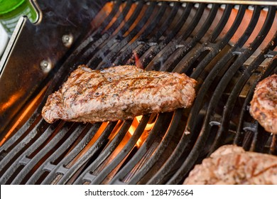 Burning Burned Juicy Steaks Sizzle on Flaming and Smoking Grill.