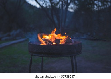 Burning camp fire at dusk in camping site, preparing for barbeque or braai, outdoors activity in South Africa. Selective focus on fire and firewood, very shallow depth of field, cold toned image.