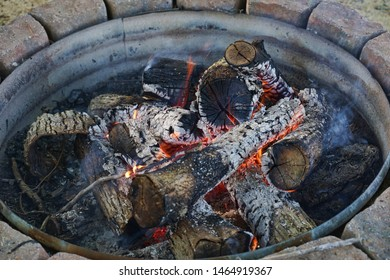 Burning campfire with several hot logs. Flames, soot, heat, smoke from a wood campfire.