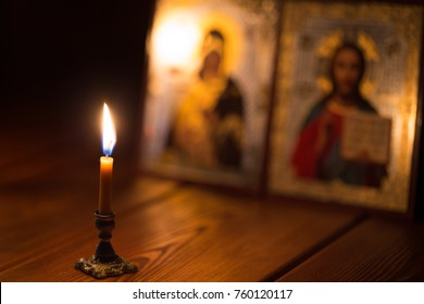 A burning candle against the background of orthodox icons in a dark room