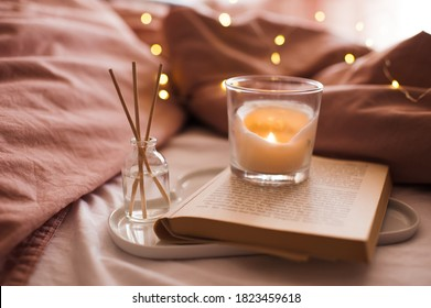 Burning candle with aroma sticks in bottle on tray with open book in bed over glowing Christmas lights close up. Cozy atmosphere at home. Good morning. Selective focus.  - Shutterstock ID 1823459618