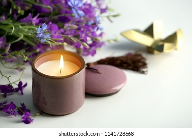 Burning candle and beautiful flowers on white table