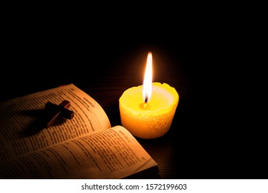 Burning candle and Bible . The psalms . Holy book  .  told in the Bible's New Testament , on a black background . Christian cross .