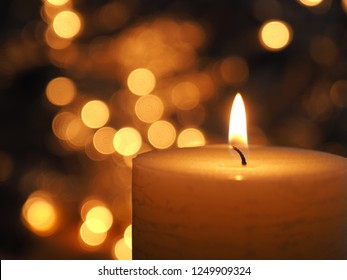 Burning candle with blurred Christmas lights