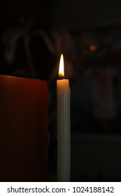 A burning candle and a book with a cross