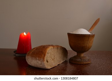 Burning candle with bread and sult still life.