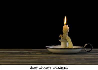Burning candle in a candlestick isolated on a black background.