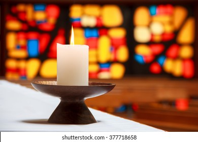 burning candle in a church with the stained-glass window at the background. Location: New Zealand, North Island, Wellington