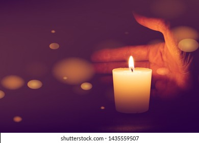 Burning candle covered with a female hand and bokeh