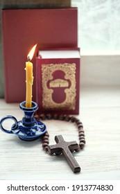 burning candle, cross, rosary beads, bible books. concept of faith, God, orthodox Church, lent, religion.