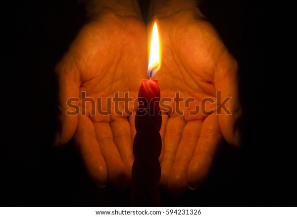 Burning candle in the dark with palms