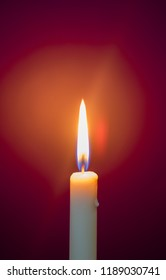 Burning candle in a dark room on a purple background