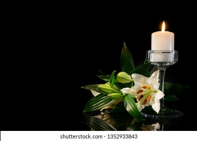 Burning candle and flowers on black background
