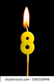 Burning candle in the form of eight figures (numbers, dates) for cake isolated on black background. The concept of celebrating a birthday, anniversary, important date, holiday, table setting