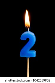 Burning candle in the form of two figures (numbers, dates) for cake isolated on black background. The concept of celebrating a birthday, anniversary, important date, holiday, table setting