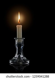 Burning candle in a glass candlestick it is isolated on the black