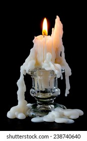 Burning candle in glass candlestick on a black background
