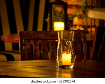 burning candle in a glass vase on a rustic wooden outdoor dining table at night