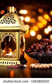 Burning candle in a golden lantern with wooden rosary and dates in a plate on bokeh background. Ramadan concept.