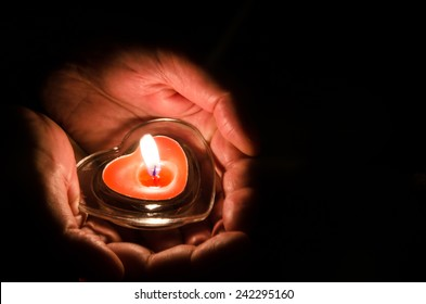 burning candle with heart shape in hands