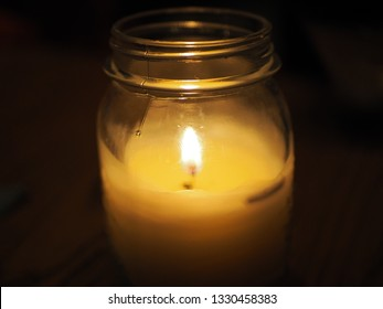 Burning candle in jar at night, in the dark. Golden light of candle flame