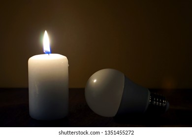 Burning candle and lamp on desktop in darkness. Power outage. Electricity missing. Blackout.