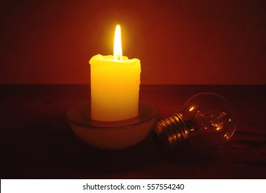Burning candle and lamp on desktop in darkness (when blackout begin, missing electricity). Broken electrical wires via storm.