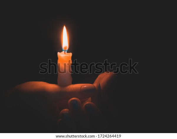 Burning candle in male hand on a black background.