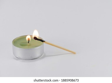 Burning candle and a match with which it was lit on a white background. Preparation for the holiday.