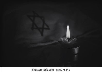 A burning candle next to the star of David on a black background. A symbol of remembrance of the victims of the genocide of the Jew in the third Reich in Germany. black and white retro photo