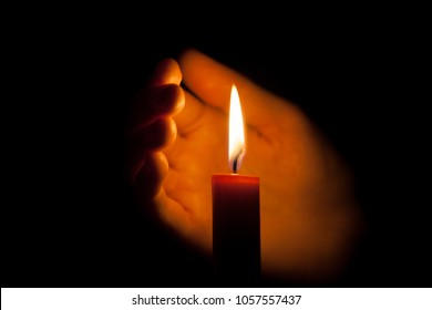 A burning candle at night, protected by the hand of a woman. Candle flame glowing on a dark background with free space for text. Close up, shallow depth of field. Symbol of life, love and light