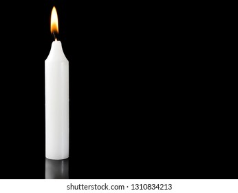Burning candle on black background with space for text.