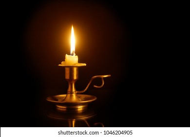 Burning candle on old brass candlestick over black background
