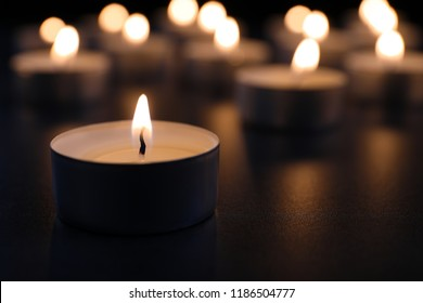 Burning candle on table in darkness, closeup with space for text. Funeral symbol