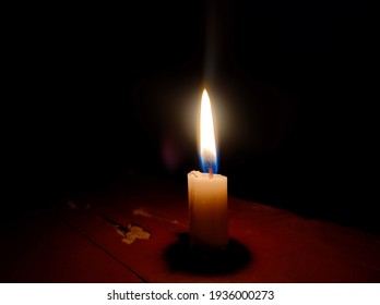 Burning candle on the wood table in the darkness.