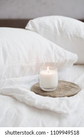 Burning candle on wooden tray on white natural linen