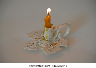 the burning candle in a porcelain candlestick