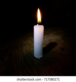 Burning candle and its shadow on square dark background