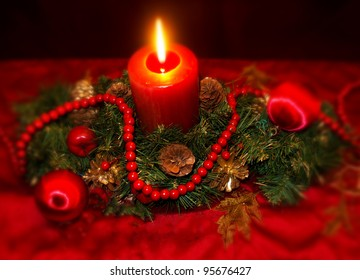 Burning candle surrounded by evergreen greenery pine cones and red beads and red Christmas ornaments.