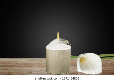 Burning candle and white calla lily on dark background. Sympathy card