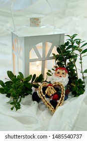burning candle in white lantern behind little santa holding straw heart sitting in lingonberry shrub on table