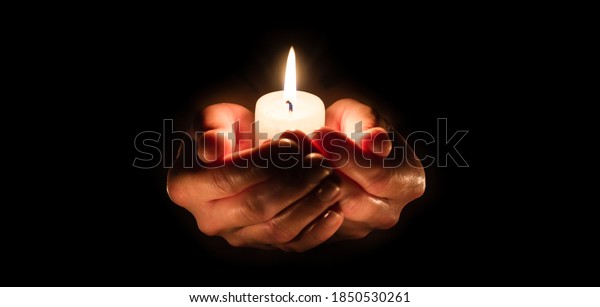 Burning candle in woman hands over black. Religious christmas spa and wellness concept - copy space.