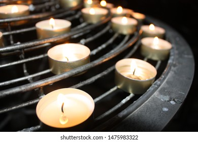 Burning candlelights or candles in a church, a catholic symbol for praying of meditating for hope, peace or love. Many burning candles on black table in darkness.