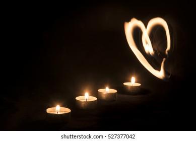 Burning candles against black background