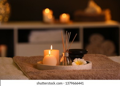 Burning candles and aromatic reed freshener on table in spa salon