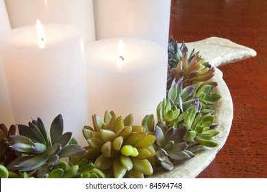Burning candles arranged on a decorative plate