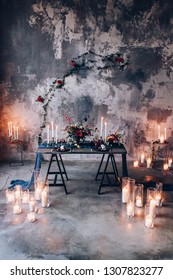 burning candles with bouquets of flowers on the table
