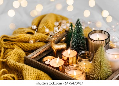 Burning candles and christmas decorations on wooden tray with warm plaid. Winter cozy style. Hygge concept.