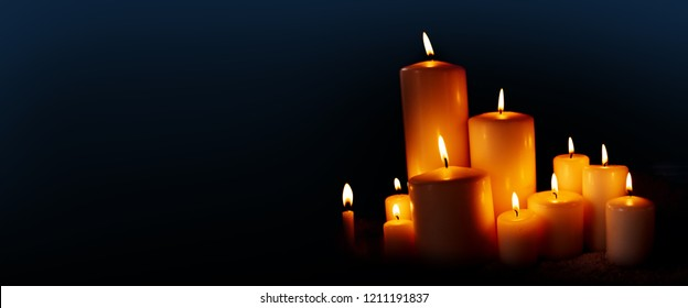 Burning candles in the dark night for a background concept